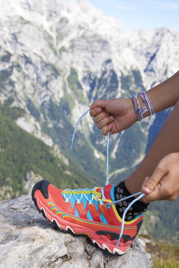 Wanderer, der Schnürsenkel, hoch in den Bergen bindet stockbild
