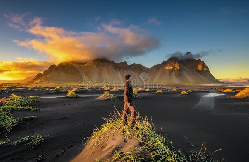 Wanderer, der Sonnenuntergang an Vestrahorn und an seinem schwarzen Sandstrand in Island genießt lizenzfreie stockfotos