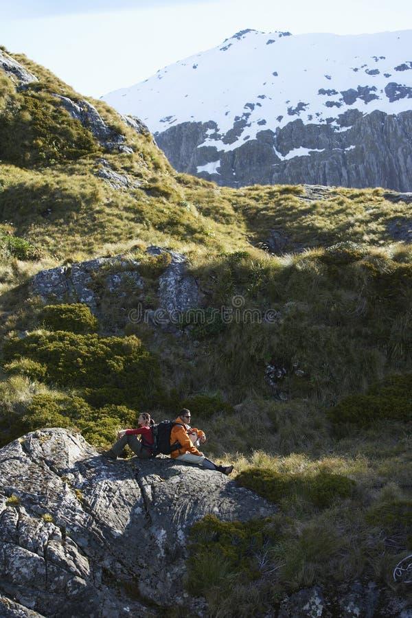Wanderer, die auf Flusssteinen im Gebirgstal sitzen stockbilder