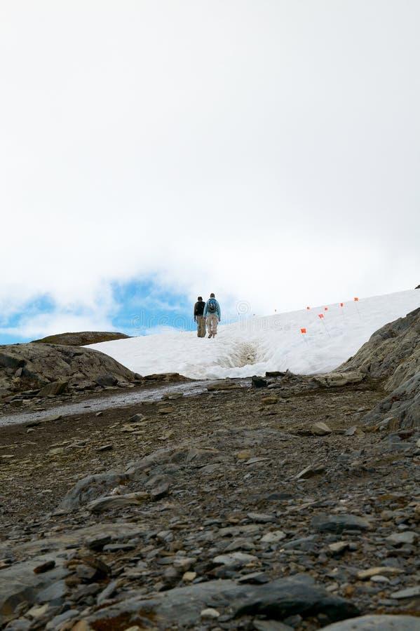 Wanderer, die in Schneeflecken in den Bergen gehen lizenzfreie stockbilder