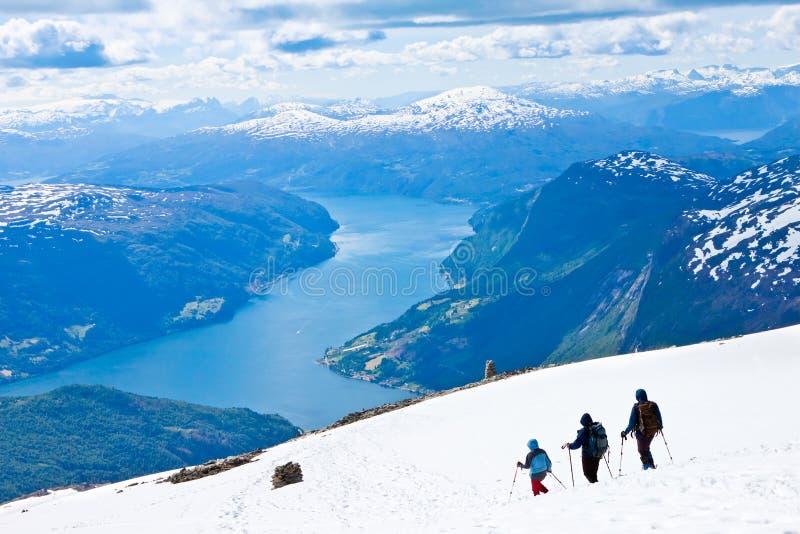 Wanderer, die unten herauf die Berge gehen stockfotografie