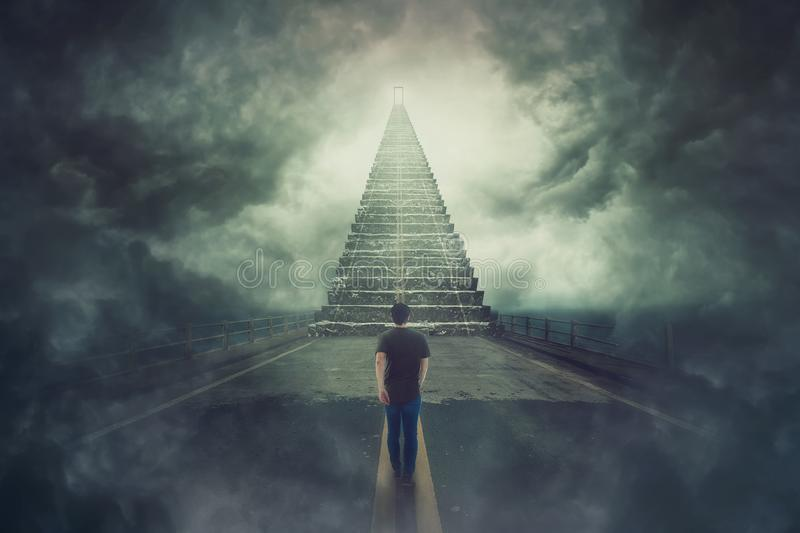 Wanderer guy confident walking a surreal road and found a magic stairway going up to a door in the sky. Mystic scene, wanderer guy confident walking a surreal royalty free stock photo