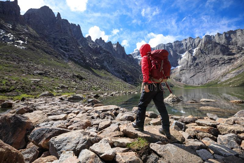 Wanderer mit dem Rucksack, der an den Bergen der großen Höhe wandert stockbild