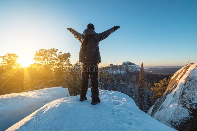 Wanderer mit einem Rucksack steht auf eine Klippe in den Wäldern von Sibirien bei Sonnenuntergang Schönes Schneepanorama von wild lizenzfreie stockfotos