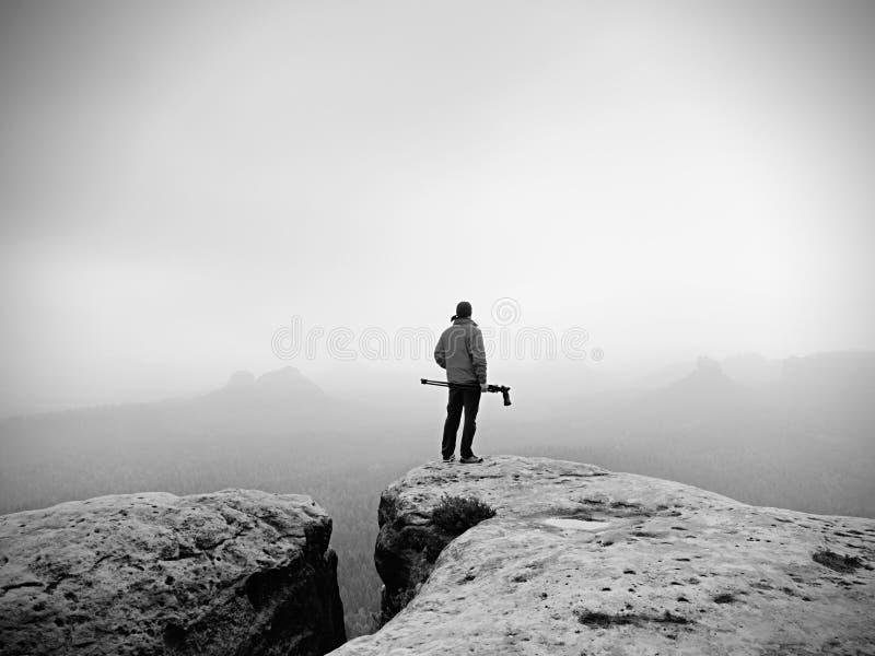Wanderer mit Kamera auf Stativ macht Foto vom felsigen Gipfel Alleinphotograph auf Gipfel lizenzfreie stockfotos