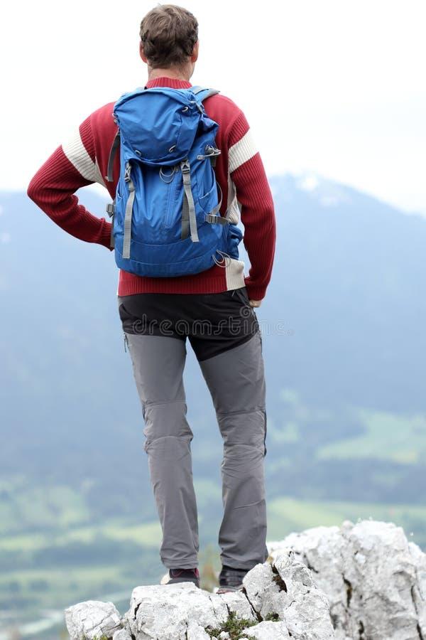 Wanderer mit Rucksack steht auf die Oberseite stockfotografie