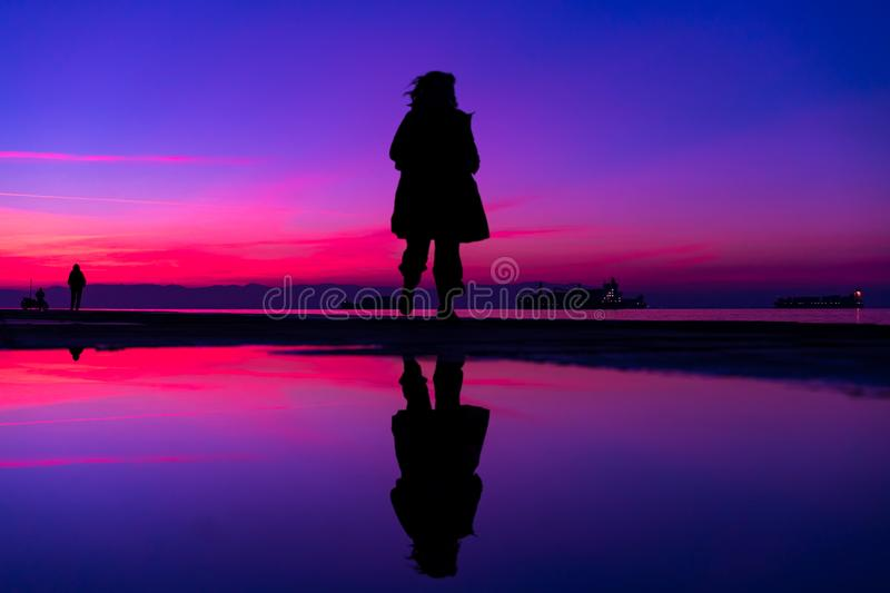 The Wanderer... Sihouette of Woman Running by the Sea, against b royalty free stock photography