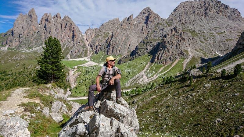 Wanderer sitzt auf einem großen Felsen Untersucht den Abstand stockbild