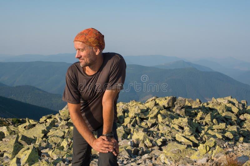 Wanderer steht auf einem Hintergrund von Bergen still stockfotos