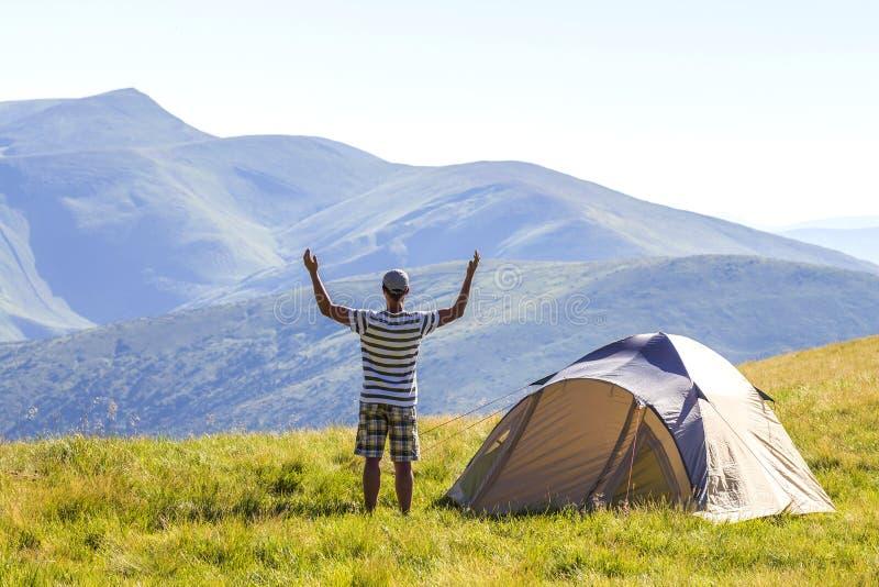 Wanderer trifft sich guten Morgen mit den angehobenen Händen, die gerade vom Zelt in den Bergen hinausgegangen werden lizenzfreie stockfotos