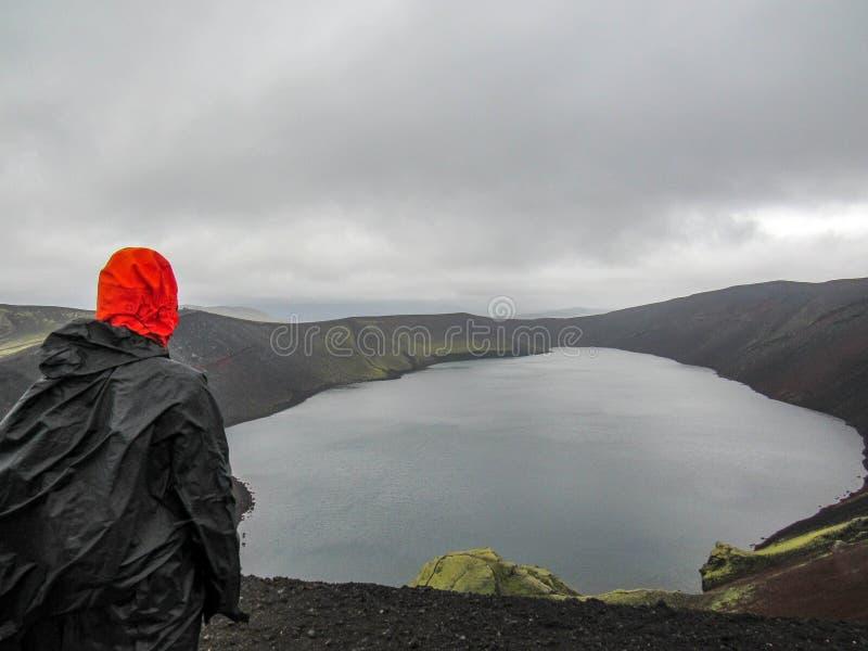 Wandererabenteurer, der im Regenmantel zurück steht im Freien wandert, Kratersee in Laugaveur-Wanderung in erstaunlicher Naturlan lizenzfreie stockbilder