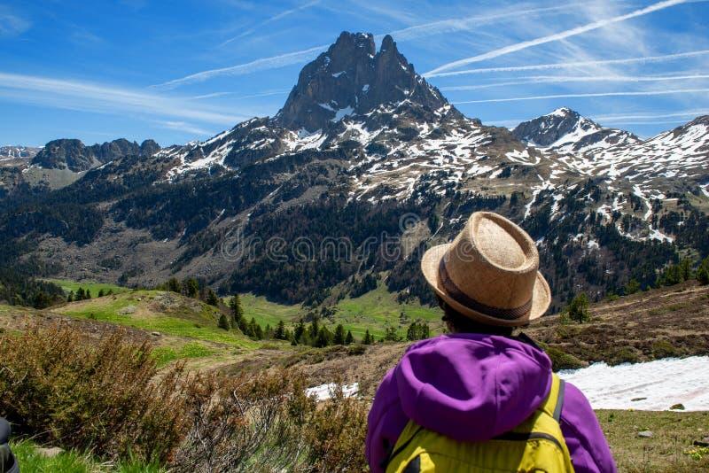 Wandererfrau, die in die franz?sischen Pyren?en-Berge, Pic DU Midi d Ossau im Hintergrund geht lizenzfreie stockfotografie