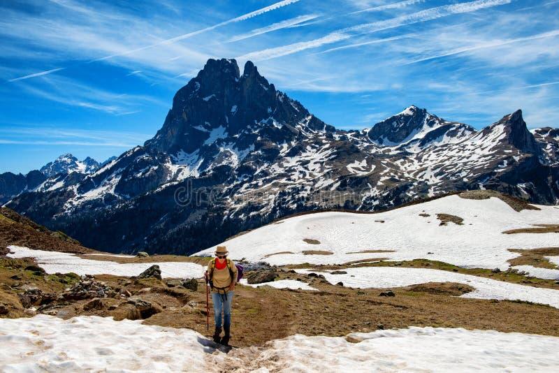 Wandererfrau, die in die franz?sischen Pyren?en-Berge, Pic DU Midi d Ossau im Hintergrund geht lizenzfreie stockfotos
