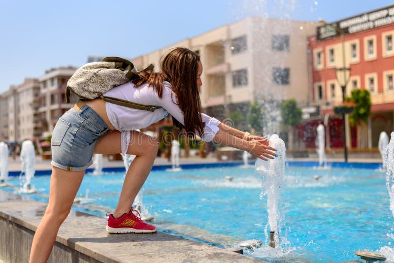 Wanderermädchen, das um die Stadt mit dem Rucksack, spielend mit Wasser im Brunnen geht lizenzfreies stockfoto