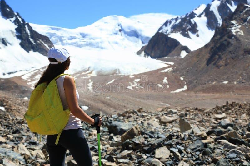 Wanderermädchen mit Rucksack am Fuß der Berge mit Gletschern stockfotografie