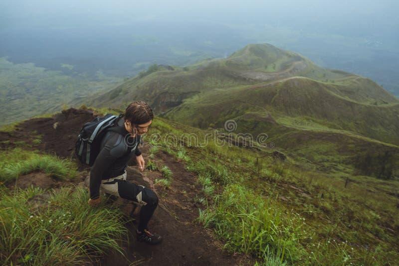 Wanderermann, der eine steile Wand im Berg klettert lizenzfreie stockbilder