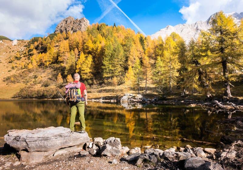 Wandererstellung auf Felsen den See und die Herbstfarben von bewundern lizenzfreie stockfotos