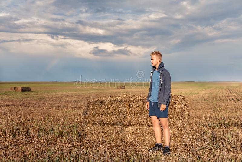 A wandering guy in a hoodie in a hood looks thoughtfully at a wheat field with a backdrop of the setting sun of a stormy sky stock photography