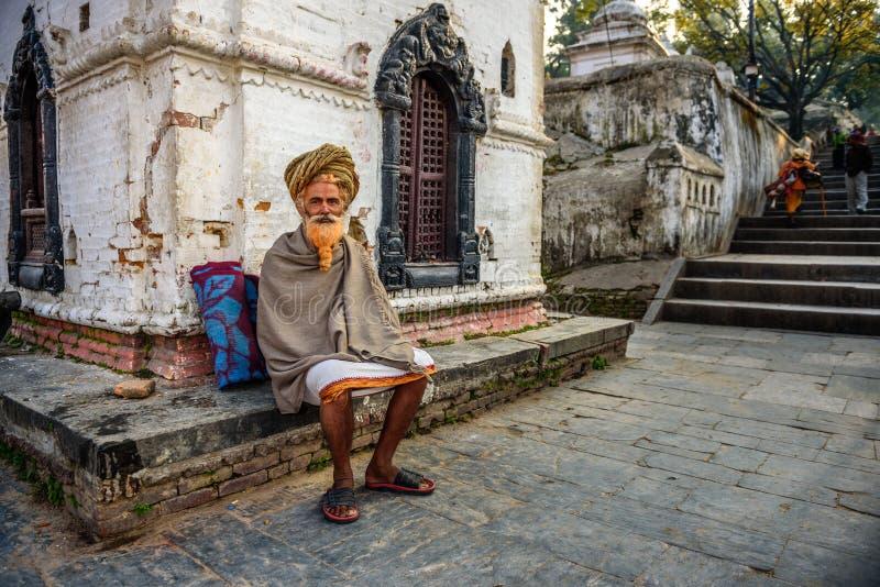 Wandering sadhu baba (holy man) in ancient Pashupatinath Temple. KATHMANDU, NEPAL - OCTOBER 21, 2015 : Wandering sadhu baba (holy man) with traditional long hair royalty free stock photo