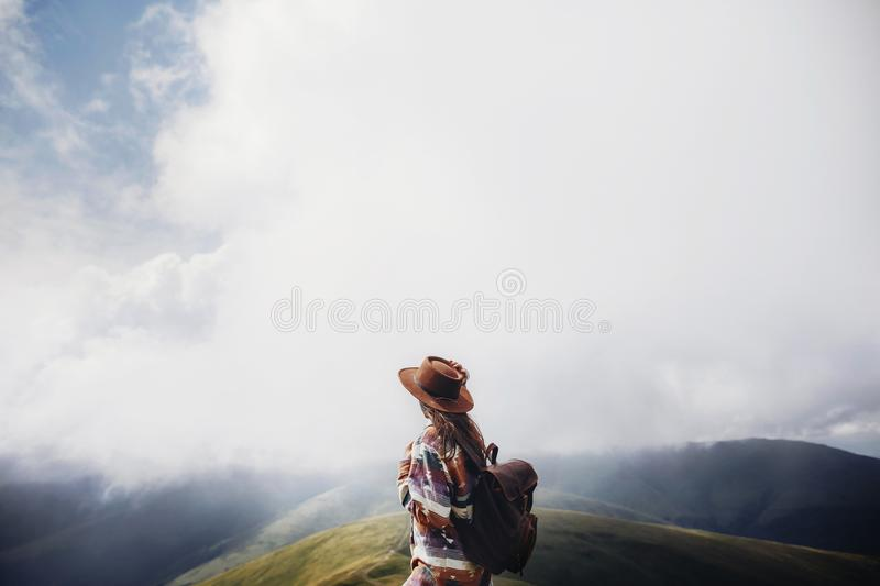 Wanderlust and travel concept. girl traveler in hat with backpack looking at clouds in mountains. stylish hipster woman exploring. On top of mountain. space for royalty free stock image