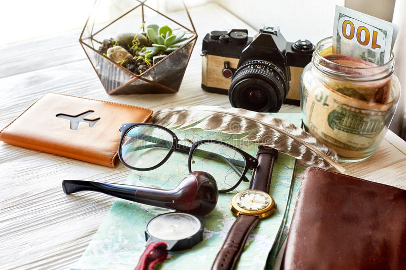 Wanderlust and travel concept. map passport money compass and glasses photo camera pipe on white wooden background. planning. Vacation. space for text. time to stock photo