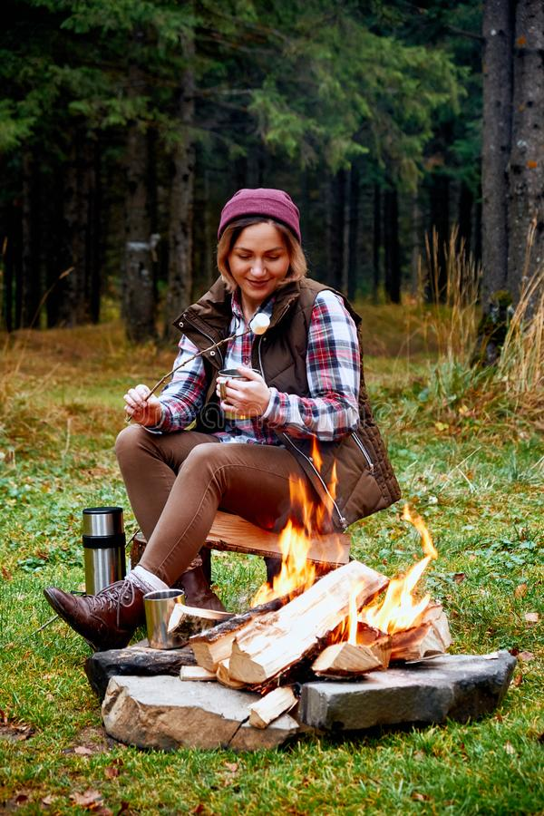 Wanderlust and Travel concept. Woman roast marshmallow candies on the campfire in forest. Spring or autumn camping royalty free stock photo