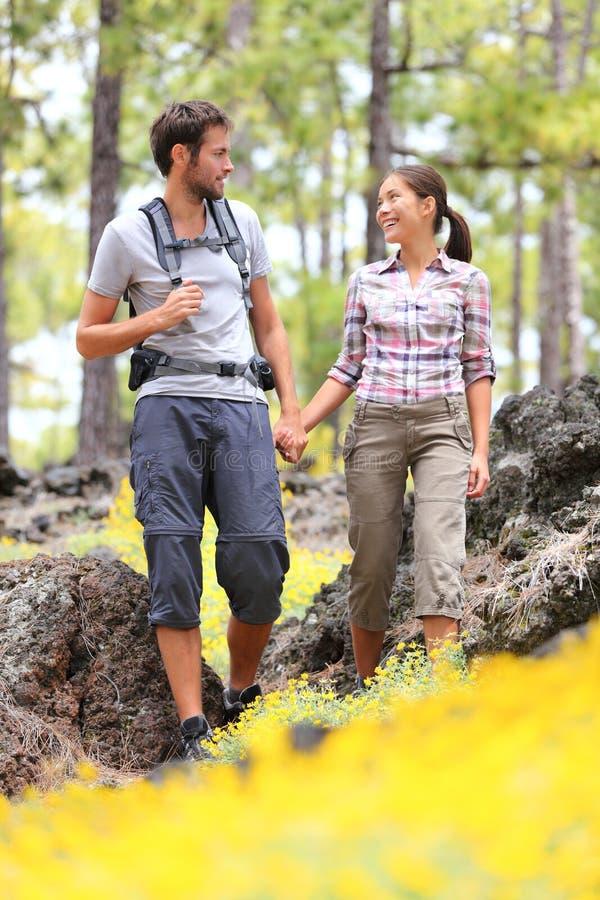 Wandern der Paare, die in Wald gehen stockbild