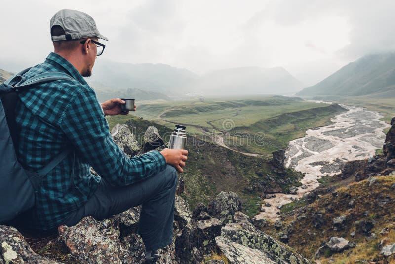 Wandern des Abenteuer-Tourismus-Ferien-Feiertags-Konzeptes Junger Reisender, der Thermosflasche in seiner Hand und Ansicht-Tal, h lizenzfreies stockbild