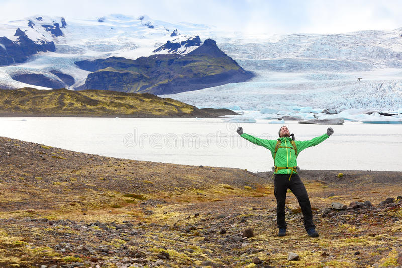 Wandern des Abenteuerreisenmannes, der glücklichem Island zujubelt lizenzfreie stockbilder