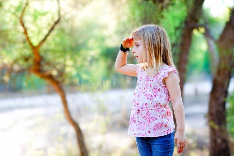 Wandern des Kindmädchens, das Hand im Kopf im Wald sucht lizenzfreies stockbild