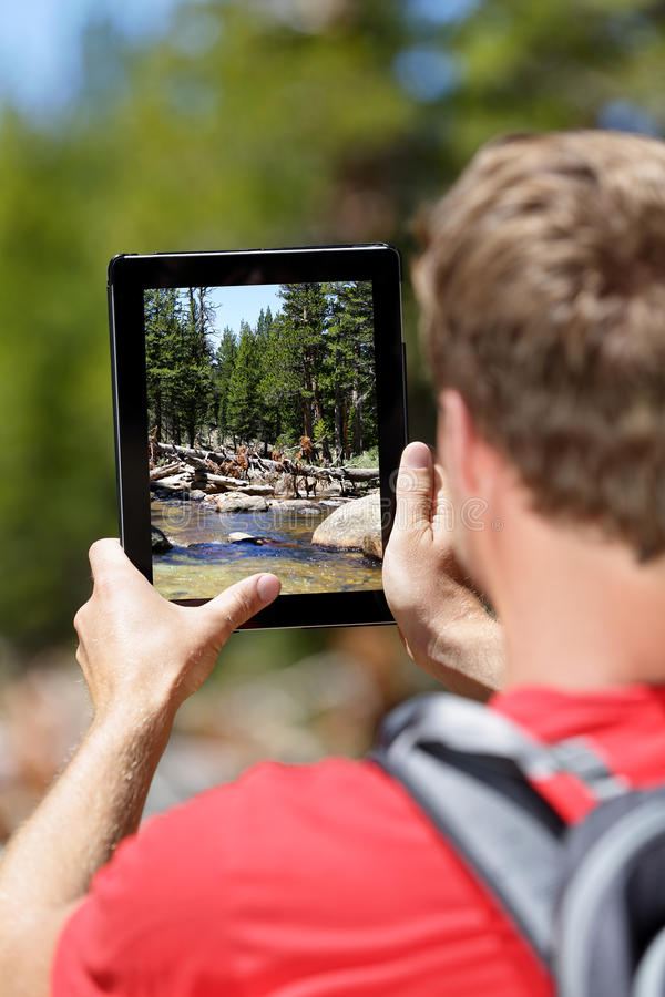 Wandern des Mannes, der Naturphotos auf Tablette macht lizenzfreies stockbild
