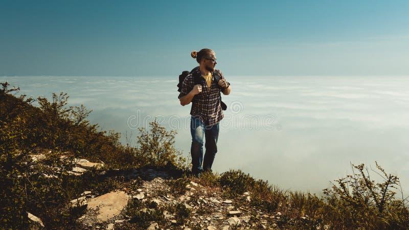 Wandern des Mannes, der zur Spitze und zu den Blicken zur Seite der Wolken klettert Motivation, Reise, Suche, Pfadfinder, Wanderl lizenzfreies stockbild