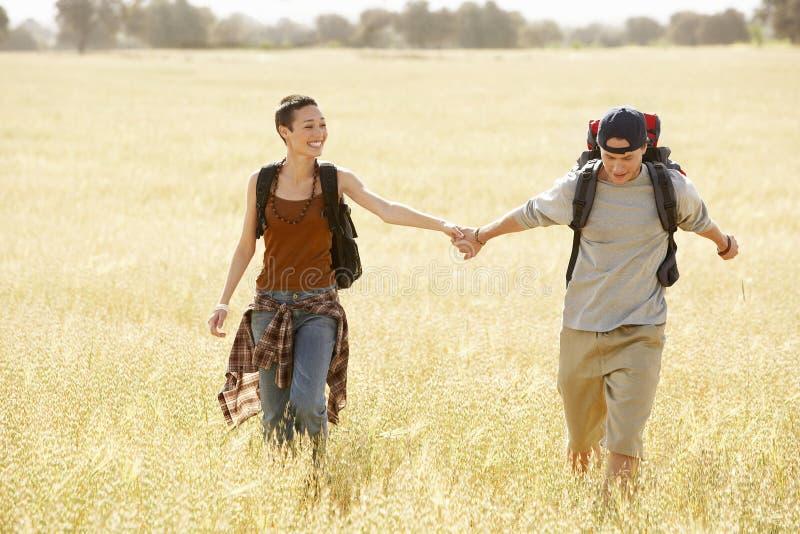 Wandern von den Paaren, die durch Feld gehen lizenzfreie stockbilder