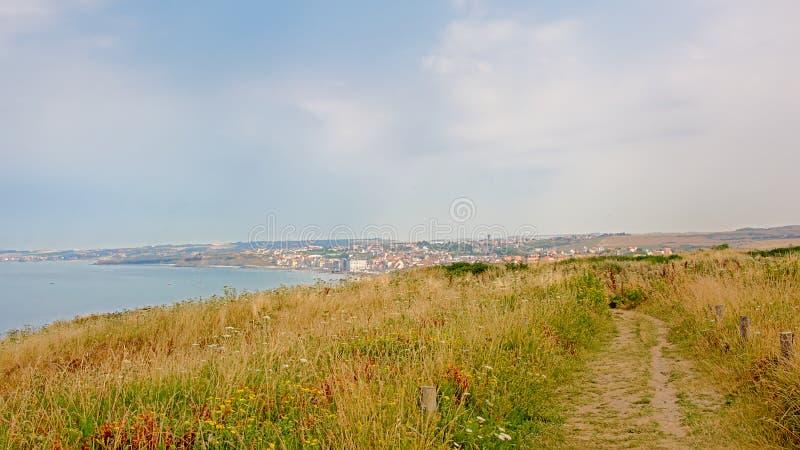 Wanderweg auf einem Gebiet auf den ciffs auf der französischen Northe-Seeküste, mit der Stadt von Wiemereux im Hintergrund lizenzfreie stockfotografie