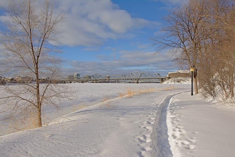 Wanderweg im Schnee entlang gefrorenem Ottawa-Fluss stockfotografie