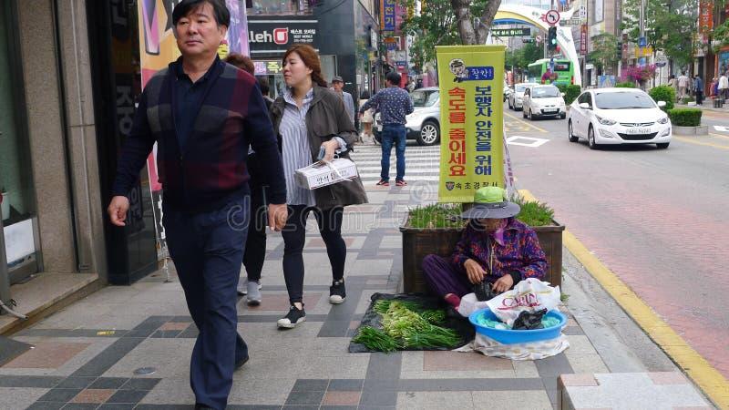 Wando/Korea-01 del sur 10 2016: Mujeres que se sientan en la calle y que venden verduras en pequeño mercado foto de archivo libre de regalías