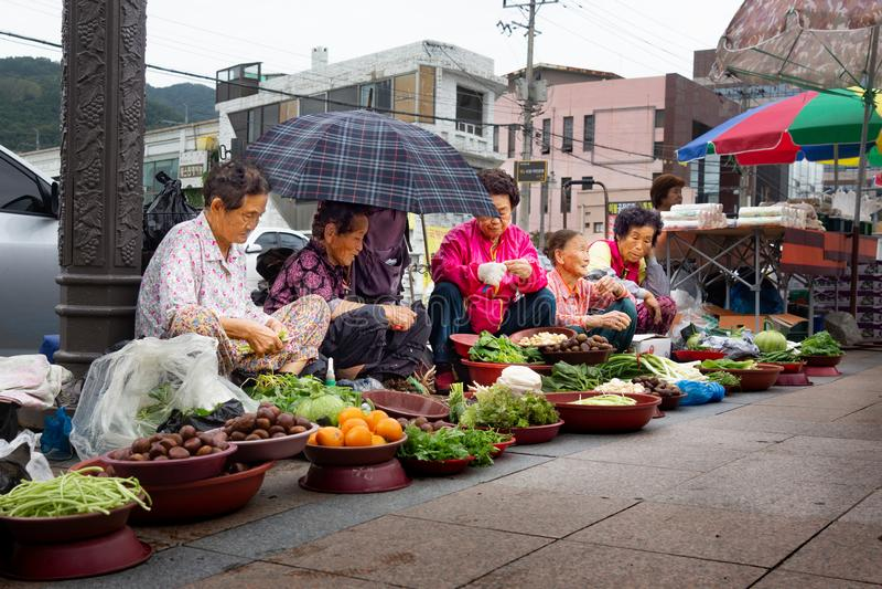 Wando/Korea-01 del sur 10 2016: Mujeres que se sientan en la calle y que venden verduras en pequeño mercado fotografía de archivo