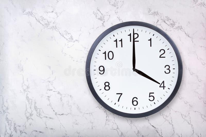 Wanduhrshow vier Uhr auf weißer Marmorbeschaffenheit Bürouhrshow 4pm oder 4am stockbilder