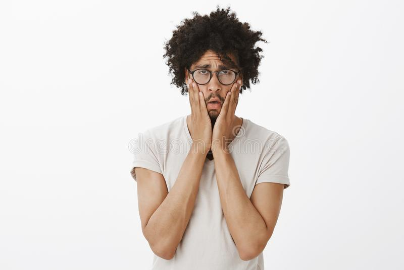 Wangen met palmen drukken en studioschot die van sombere uitgeputte en bored leuke kerel met afrokapsel in glazen, staren stock afbeeldingen