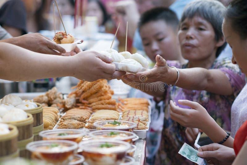 Wangfujing street, Beijing, China - 08 01 2016:Woman buying street food in Wangfujing street, a shopping street in Beijing, China royalty free stock photography