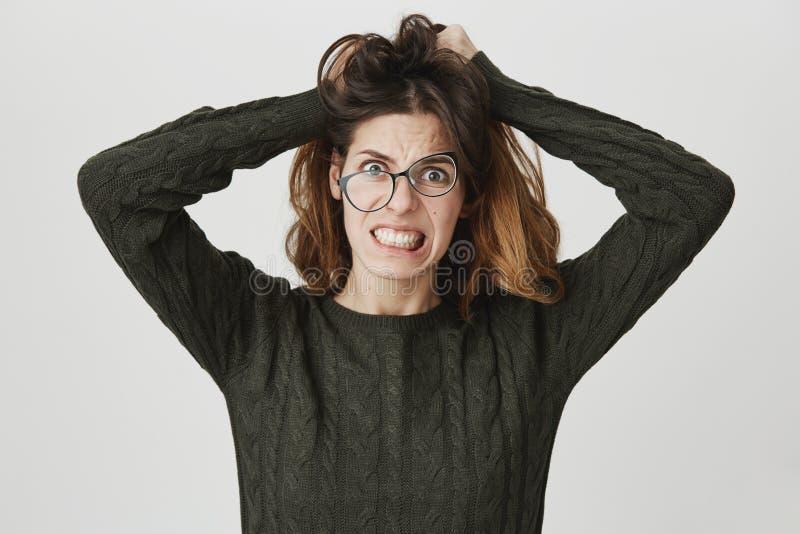 Wanhopig geërgerd wijfje die glazen dragen die uit in woede en woede tearing haar gillen die, tanden dichtklemmen, terwijl het vo royalty-vrije stock afbeeldingen