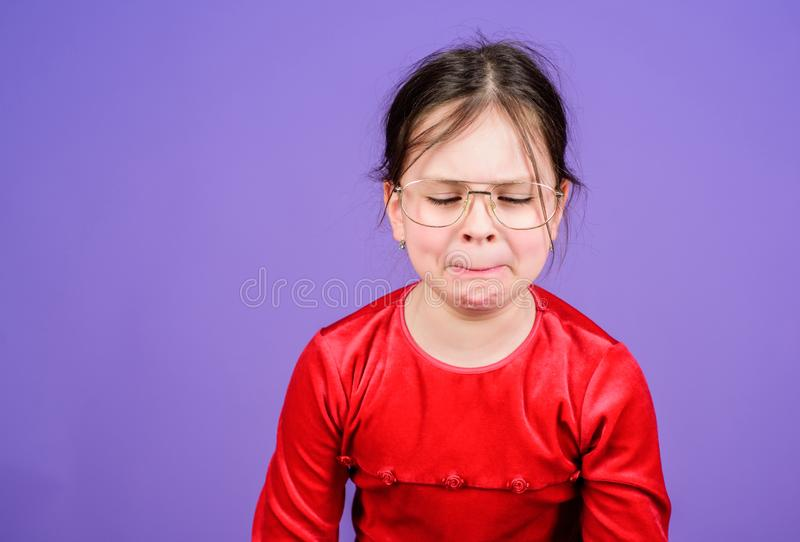 Wanhopige baby De emotionele violette achtergrond van het gezichts kleine meisje Kan niet haar gevoel tegenhouden Verloren emotio stock foto's