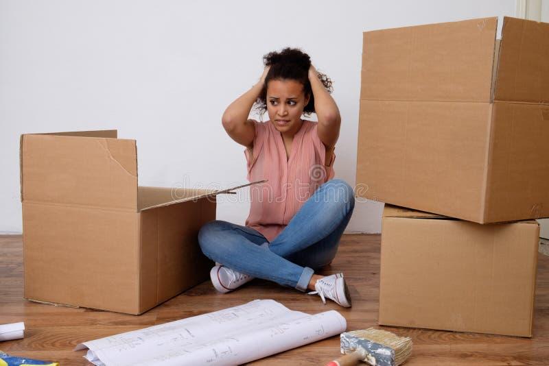 Wanhopige en vermoeide vrouw tijdens huisverhuizing stock fotografie