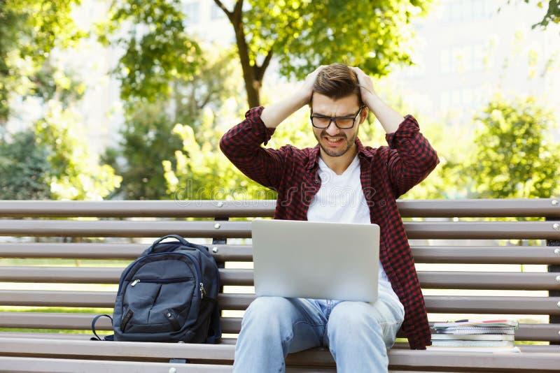 Wanhopige jonge mens die laptop in openlucht met behulp van royalty-vrije stock foto's