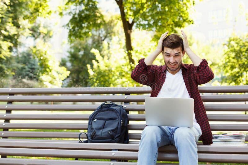 Wanhopige jonge mens die laptop in openlucht met behulp van stock fotografie