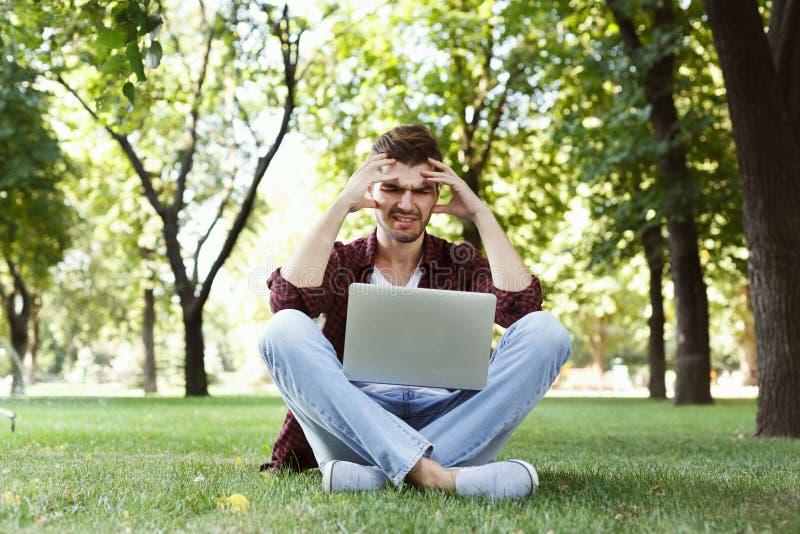Wanhopige jonge mens die laptop in openlucht met behulp van stock afbeelding
