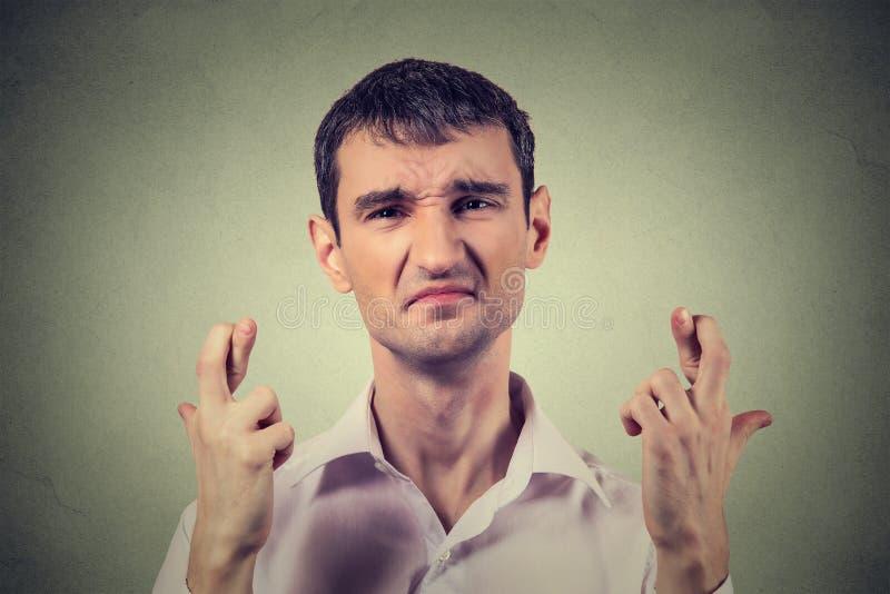 Wanhopige mens die een wens maken die vingers kruisen stock afbeelding