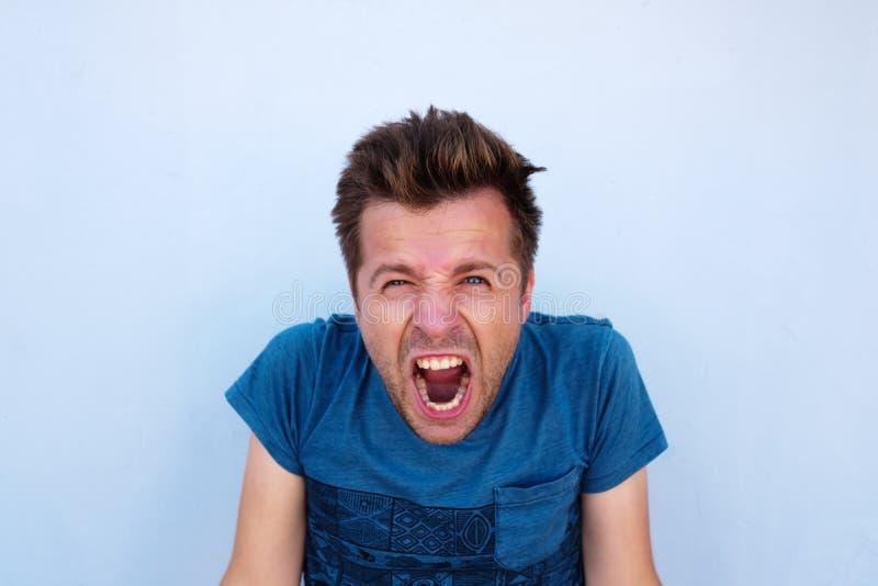 Wanhopige woedend woedde mens die in blauw overhemd luid het hebben van zijn ogenhoogtepunt gillen van woede stock afbeeldingen