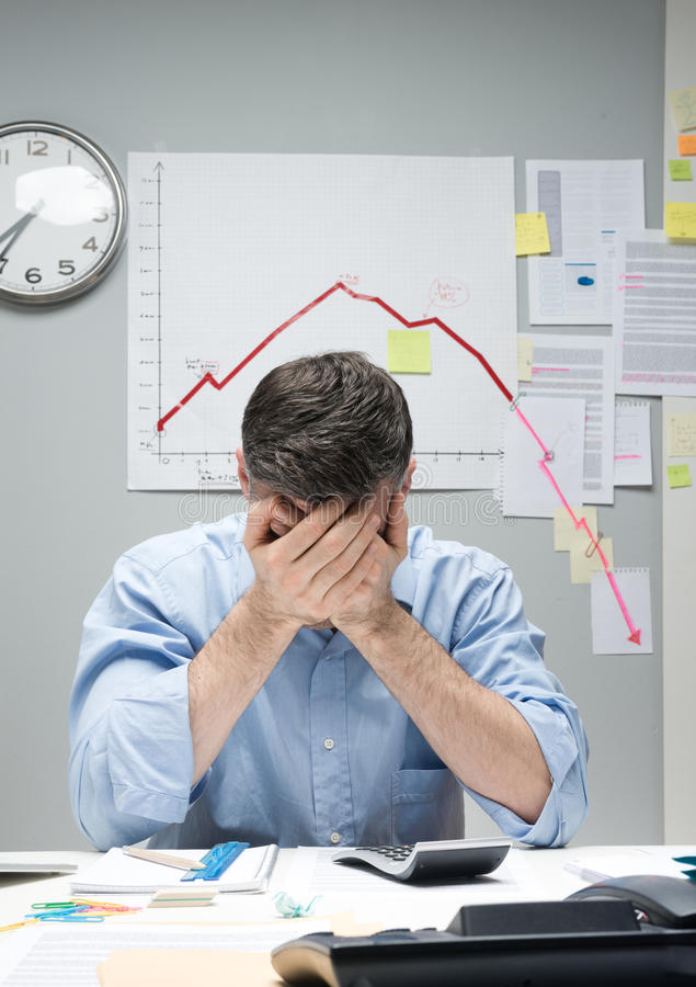Wanhopige zakenman met negatieve bedrijfsgrafiek stock foto