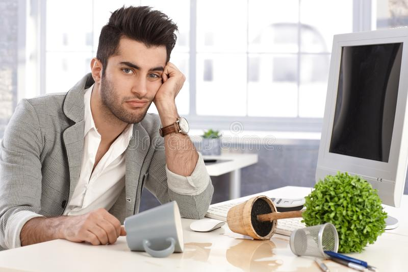 Wanhopige zakenmanzitting bij bureau in wanorde stock afbeeldingen